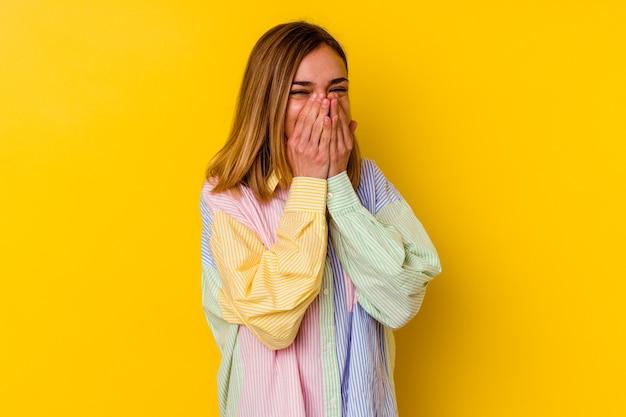 Młody kaukaski chuda kobieta na żółtym tle, śmiejąc się z czegoś, zakrywając usta rękami.