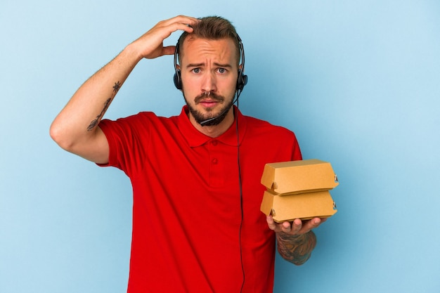 Młody kaukaski dostawca z tatuażami, trzymający hamburgery na białym tle na niebieskim tle, będąc w szoku, przypomniała sobie ważne spotkanie.