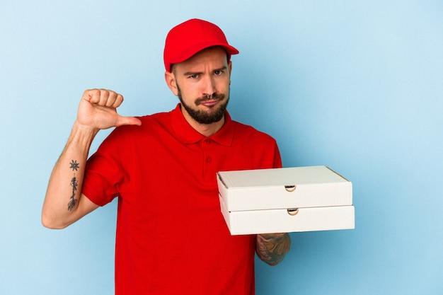 Młody kaukaski dostawca z tatuażami, trzymający pizze na białym tle na niebieskim tle, czuje się dumny i pewny siebie, przykład do naśladowania.