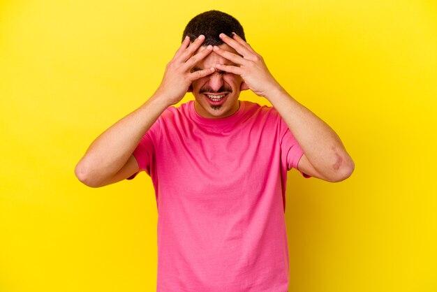 Młody kaukaski fajny mężczyzna na białym tle na żółtej ścianie o ból głowy, dotykając przedniej części twarzy