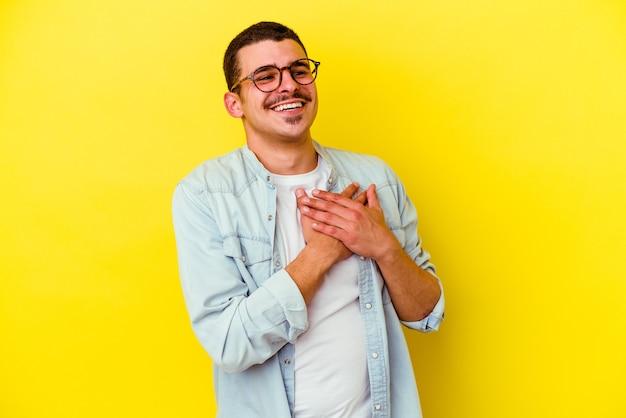 Młody kaukaski fajny mężczyzna na żółtym tle ma przyjazny wyraz, przyciskając dłoń do klatki piersiowej. koncepcja miłości.