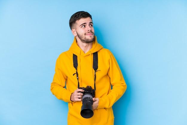 Młody kaukaski fotograf mężczyzna na białym tle marzy o osiągnięciu celów
