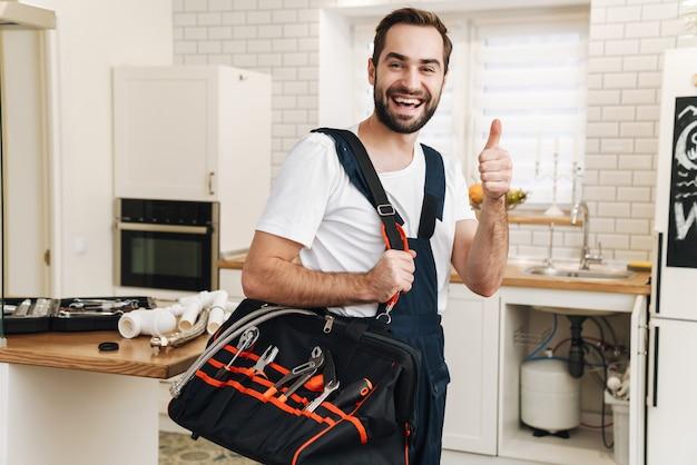 Młody kaukaski hydraulik w mundurze trzymający torbę ze sprzętem i wskazujący kciuk w górę podczas pracy w mieszkaniu