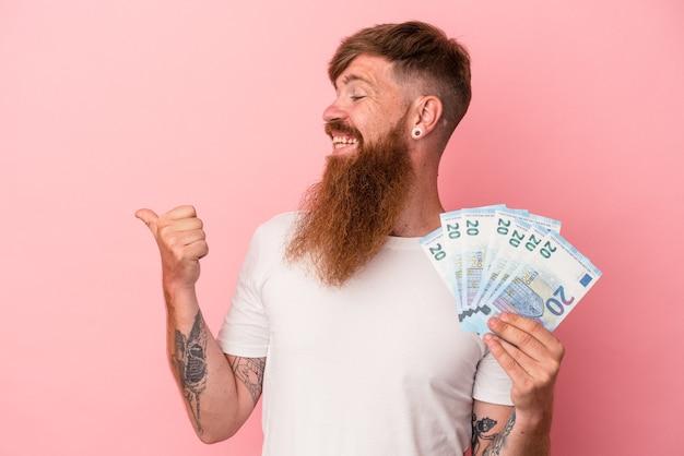 Młody kaukaski imbir człowiek z długą brodą trzymając banknoty na białym tle na różowym tle wskazuje kciukiem od palca, śmiejąc się i beztroski.