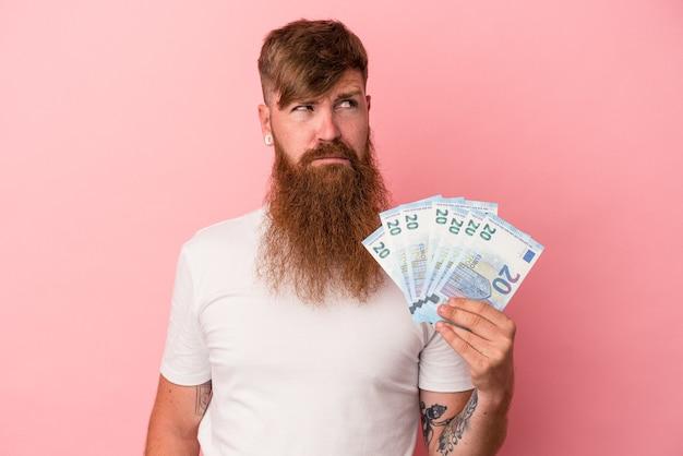 Młody kaukaski imbir z długą brodą trzymający banknoty na białym tle na różowym tle zdezorientowany, czuje się niepewny i niepewny.