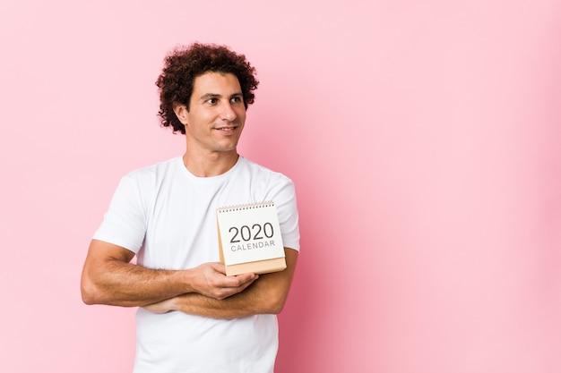 Młody kaukaski kędzierzawy mężczyzna trzyma kalendarz 2020 uśmiecha się pewnie ze skrzyżowanymi rękami.