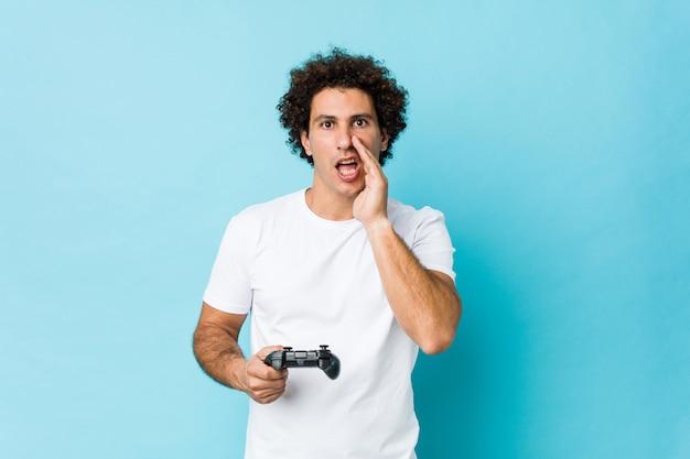 Młody kaukaski kędzierzawy mężczyzna trzyma kontroler gier krzyczy podekscytowany do przodu.