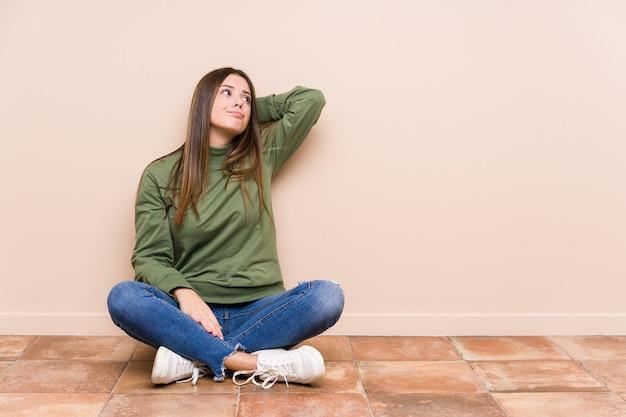 Młody kaukaski kobieta siedzi na podłodze na białym tle dotykając tyłu głowy, myśląc i dokonując wyboru.