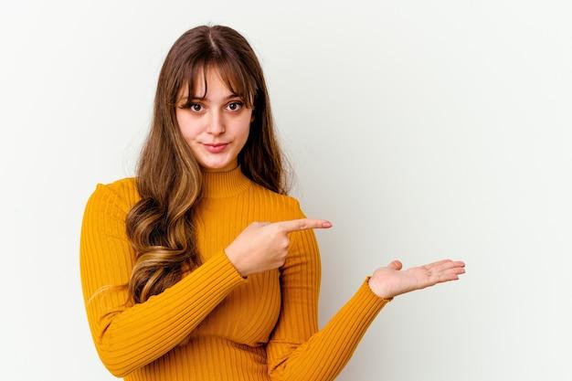 Młody kaukaski kobieta śliczna na białym podekscytowany, trzymając miejsce na kopię na dłoni.