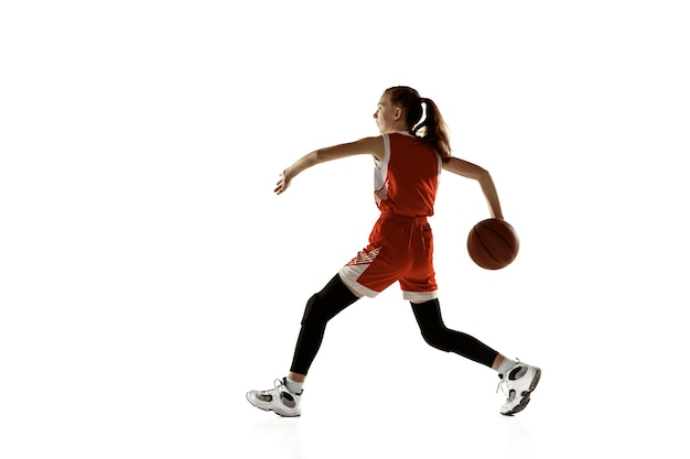 Młody kaukaski koszykarz kobiet w akcji, ruch w biegu na białym tle. rudowłosa sportowa dziewczyna. pojęcie sportu, ruchu, energii i dynamicznego, zdrowego stylu życia. trening.