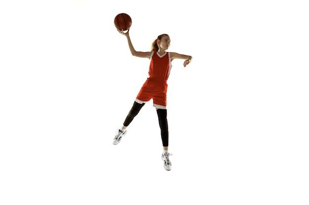 Młody kaukaski koszykarz płci żeńskiej w akcji, ruch w skoku na białym tle. rudowłosa sportowa dziewczyna. pojęcie sportu, ruchu, energii i dynamicznego, zdrowego stylu życia. trening.