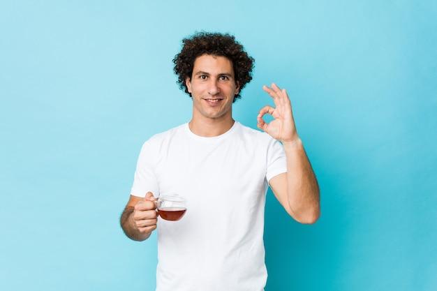 Młody kaukaski kręcone mężczyzna trzyma filiżankę herbaty wesoły i pewny siebie, pokazując ok gest.