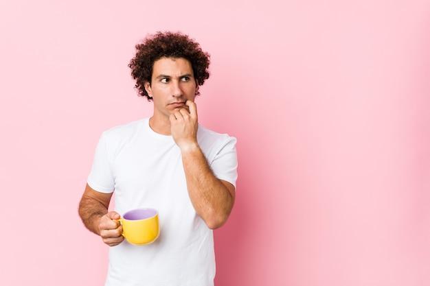 Młody kaukaski kręcone mężczyzna trzyma filiżankę herbaty zrelaksowany, myśląc o czymś, patrząc na przestrzeń kopii.