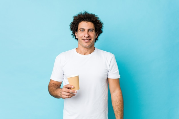Młody kaukaski kręcone mężczyzna trzyma kawę na wynos szczęśliwy, uśmiechnięty i wesoły.