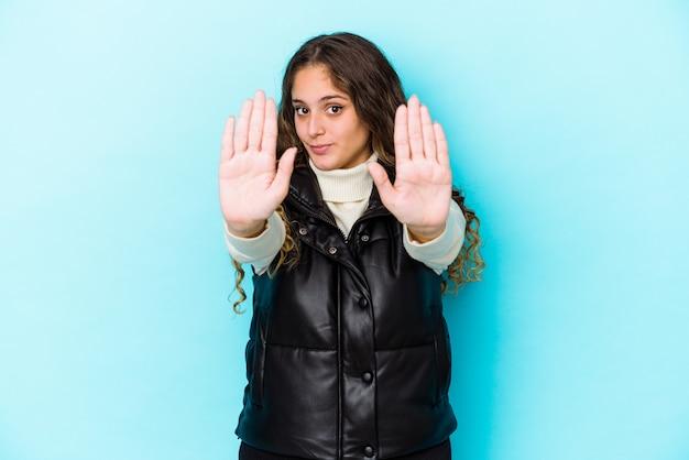 Młody kaukaski kręcone włosy kobieta na białym tle stojący z wyciągniętą ręką pokazujący znak stopu, uniemożliwiając ci.