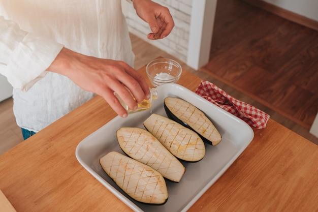 Młody kaukaski kucharz w domu sypie bakłażany solą, żeby zrobiły się papkowate