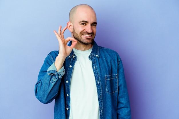 Młody kaukaski łysy mężczyzna na fioletowej ścianie mruga okiem i trzyma w porządku gest ręką