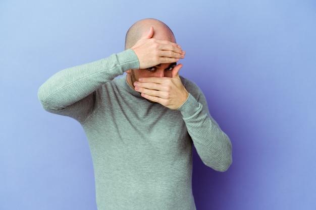 Młody kaukaski łysy mężczyzna na fioletowej ścianie mruga przez palce, zawstydzona zakrywająca twarz.
