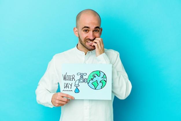 Młody kaukaski łysy mężczyzna obchodzi światowy dzień wody na białym tle na niebieskim tle gryzienie paznokci