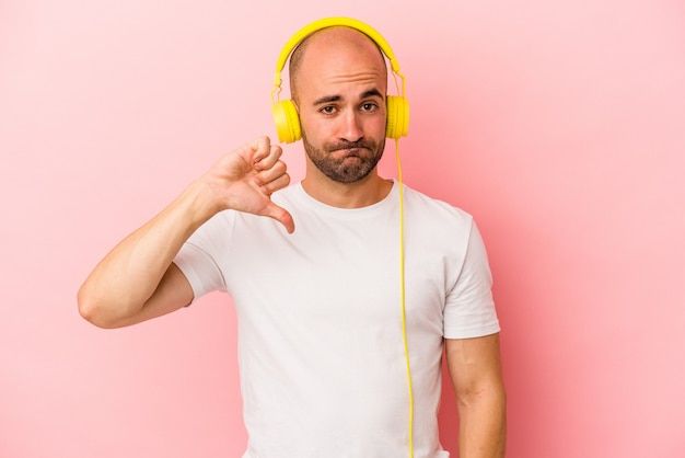 Młody kaukaski łysy mężczyzna słucha muzyki na białym tle na różowym tle pokazując gest niechęci, kciuk w dół. koncepcja niezgody.