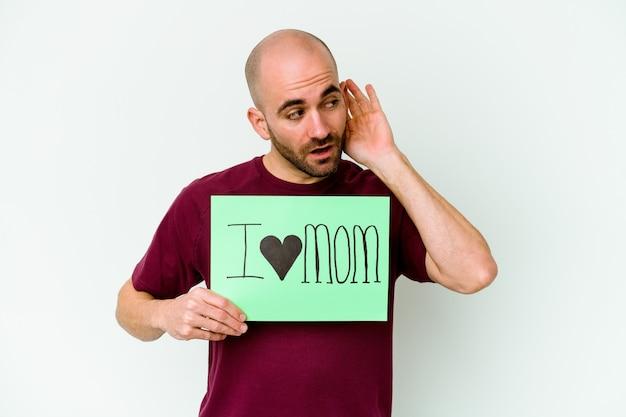 Młody kaukaski łysy mężczyzna trzyma afisz kocham mamę na białym tle na żółtej ścianie, próbując słuchać plotek.
