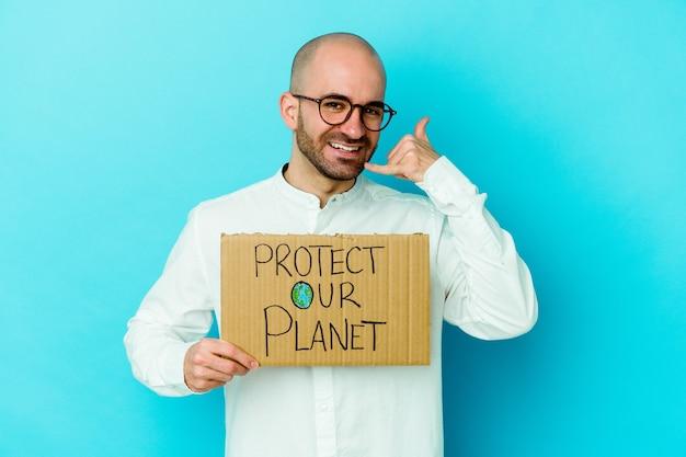 Młody kaukaski łysy mężczyzna trzyma afisz ochrony naszej planety na białym tle na fioletowym tle pokazujący gest połączenia z telefonu komórkowego palcami.