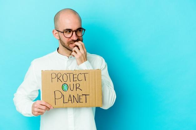 Młody kaukaski łysy mężczyzna trzyma afisz ochrony naszej planety na białym tle na fioletowym tle zrelaksowany myśląc o czymś patrząc na miejsce na kopię.