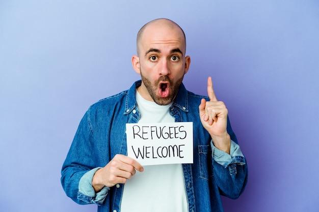 Młody kaukaski łysy mężczyzna trzyma afisz powitalny uchodźców na białym tle na niebieskiej ścianie o pomysł, koncepcja inspiracji.