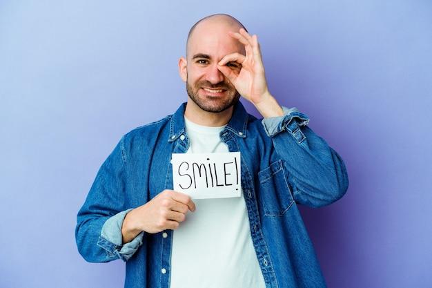 Młody kaukaski łysy mężczyzna trzyma afisz uśmiech na białym tle na fioletowej ścianie podekscytowany utrzymując ok gest na oko.