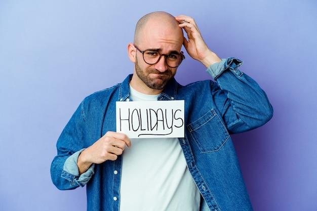 Młody kaukaski łysy mężczyzna trzyma afisz wakacje na białym tle na niebieskim tle będąc w szoku, przypomniała sobie ważne spotkanie.
