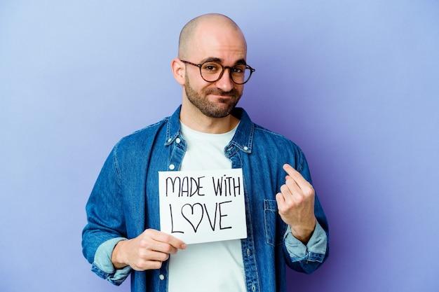 Młody kaukaski łysy mężczyzna trzyma afisz wykonany z miłością na białym tle na fioletowym tle, wskazując palcem na ciebie, jakby zapraszając się bliżej.