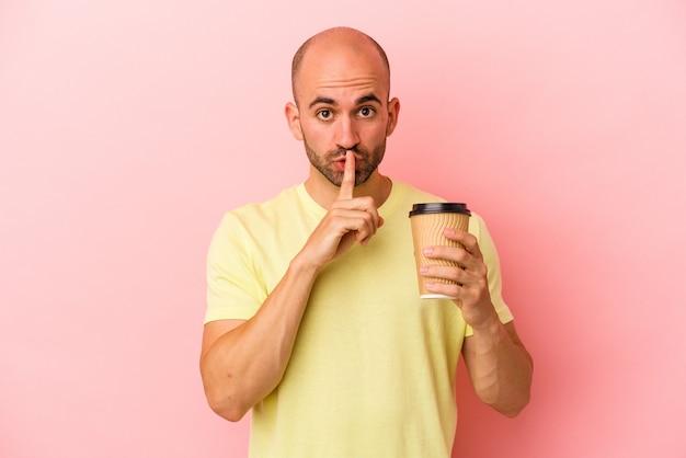 Młody kaukaski łysy mężczyzna trzyma kawę na wynos na białym tle na różowym tle zachowując tajemnicę lub prosząc o ciszę.