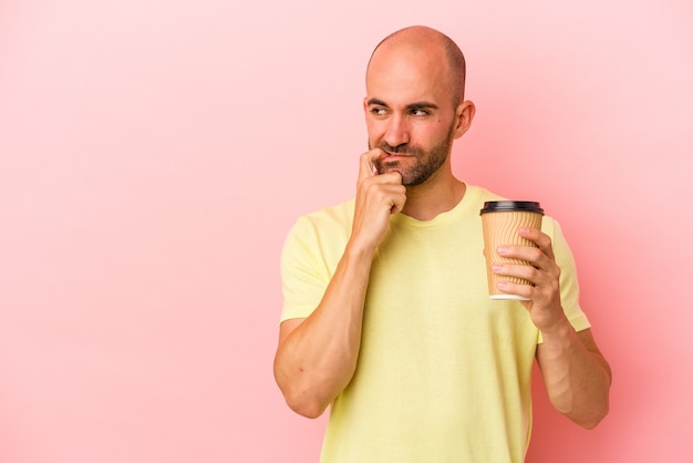 Młody kaukaski łysy mężczyzna trzyma kawę na wynos na białym tle na różowym tle zrelaksowany myśląc o czymś patrząc na miejsce na kopię.