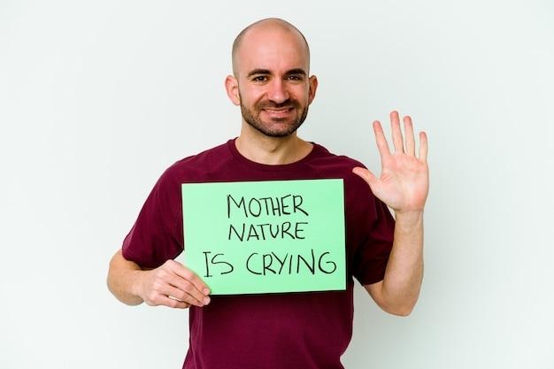 Młody kaukaski łysy mężczyzna trzyma matkę naturę płacz na białym tle uśmiechnięty wesoły pokazując numer pięć palcami.