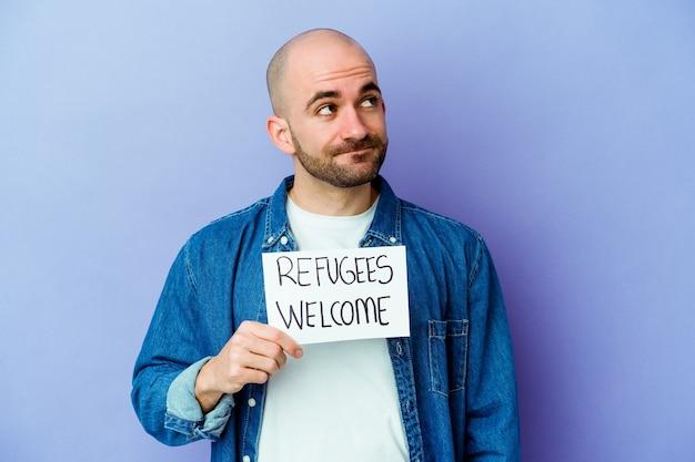 Młody kaukaski łysy mężczyzna trzyma plakietkę witamy uchodźców na białym tle