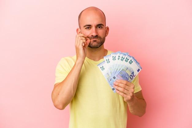 Młody kaukaski łysy mężczyzna trzyma rachunki na białym tle na różowym tle z palcami na ustach zachowując tajemnicę.