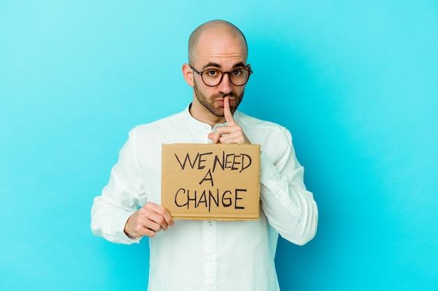 Młody kaukaski łysy mężczyzna trzyma tabliczkę zmiany na fioletowym tle z zachowaniem tajemnicy lub prośbą o ciszę.
