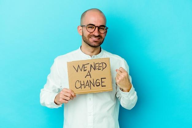Młody kaukaski łysy mężczyzna trzymający a potrzebujemy plakietki zmiany na fioletowo, wskazującej palcem na ciebie, jakby zapraszając, podejdź bliżej.