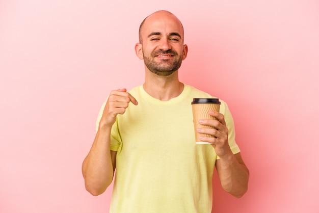 Młody kaukaski łysy mężczyzna trzymający kawę na wynos na białym tle na różowym tle osoba wskazująca ręcznie na miejsce na koszulkę, dumna i pewna siebie