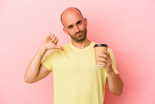 Młody kaukaski łysy mężczyzna trzymający kawę na wynos na różowym tle czuje się dumny i pewny siebie, przykład do naśladowania.