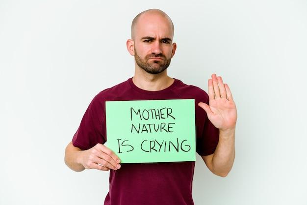 Młody kaukaski łysy mężczyzna trzymający matkę naturę płaczący na białej stojącej z wyciągniętą ręką pokazujący znak stopu, uniemożliwiając ci.