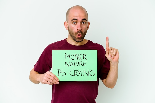 Młody kaukaski łysy mężczyzna trzymający matkę naturę płaczący na białym tle posiadający świetny pomysł, pojęcie kreatywności.