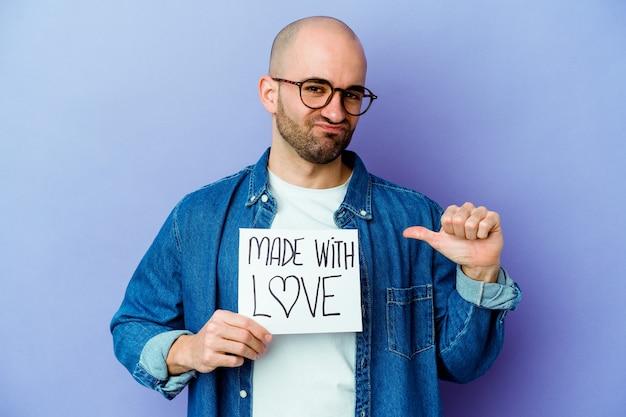 """Młody kaukaski łysy mężczyzna trzymający napis """"made with love"""" na fioletowej ścianie czuje się dumny i pewny siebie, przykład do naśladowania."""