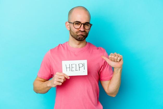 Młody kaukaski łysy mężczyzna trzymający plakietkę pomocy na fioletowej ścianie czuje się dumny i pewny siebie, przykład do naśladowania.