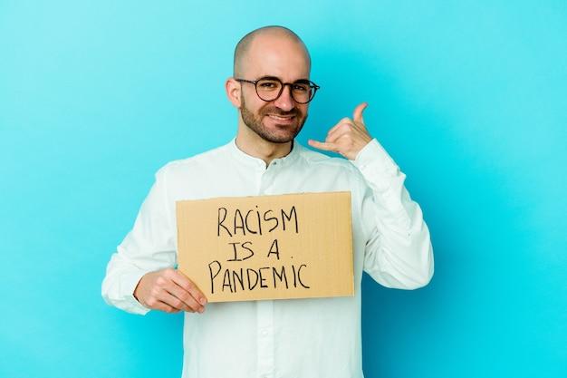 Młody kaukaski łysy mężczyzna trzymający rasizm jest pandemią na białym tle pokazujący gest telefonu komórkowego palcami.