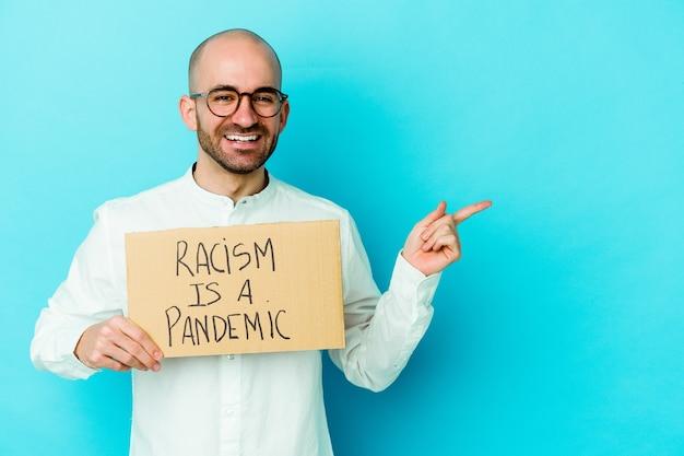 Młody kaukaski łysy mężczyzna trzymający rasizm to pandemia odizolowana na białej ścianie, uśmiechnięta i wskazująca na bok, pokazująca coś w pustej przestrzeni