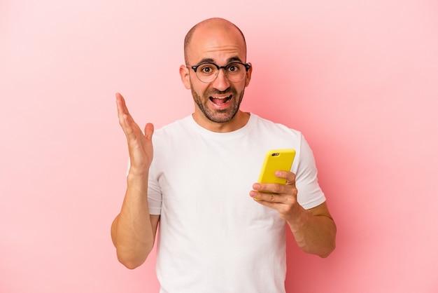 Młody kaukaski łysy mężczyzna trzymający telefon komórkowy na białym tle na różowym tle otrzymujący miłą niespodziankę, podekscytowany i podnoszący ręce.