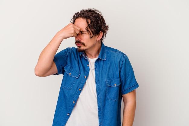 Młody kaukaski mężczyzna ból głowy, dotykając przedniej części twarzy.