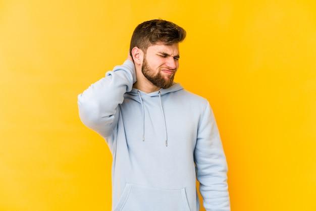 Młody kaukaski mężczyzna cierpi na ból szyi z powodu siedzącego trybu życia.