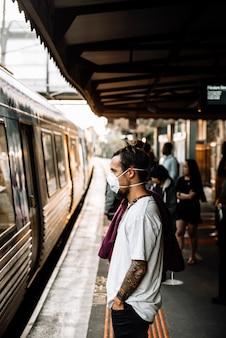 Młody kaukaski mężczyzna czeka na pociąg i nosi maskę